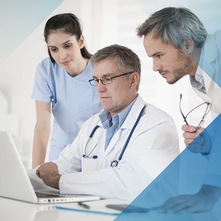 Zwei Ärzte und eine Arztin schauen sich auf Laptop Impella Herzpumpen an