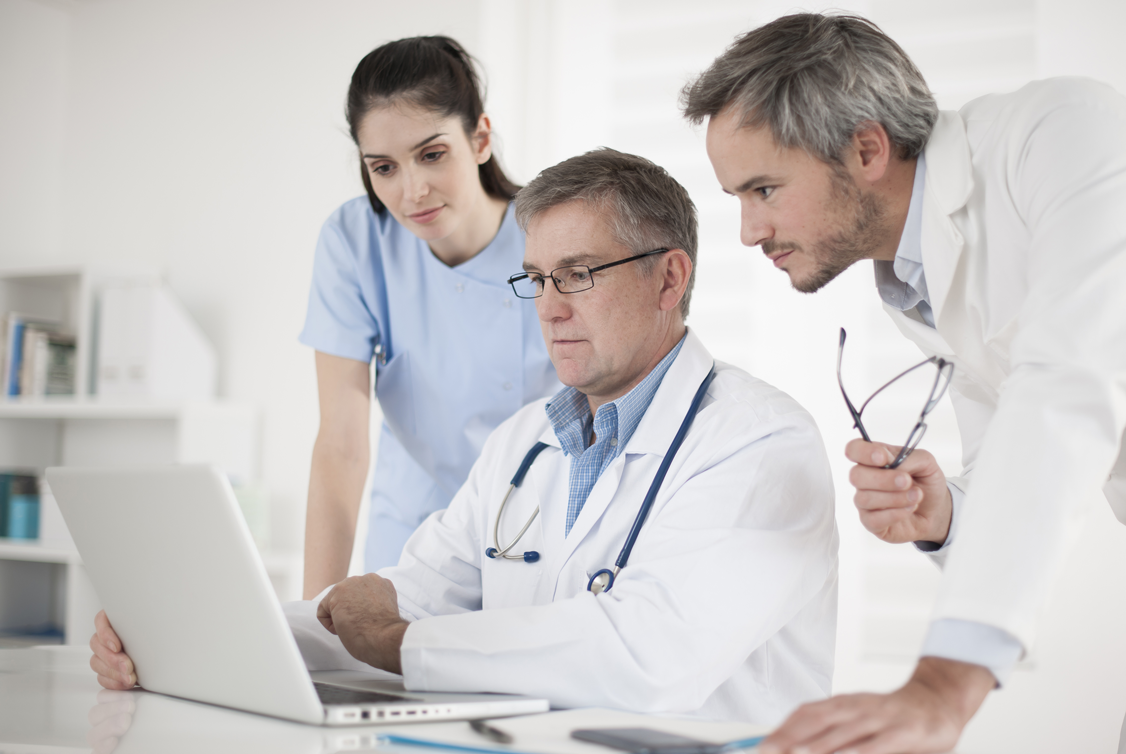 Image of three health care providers gathering around a computer