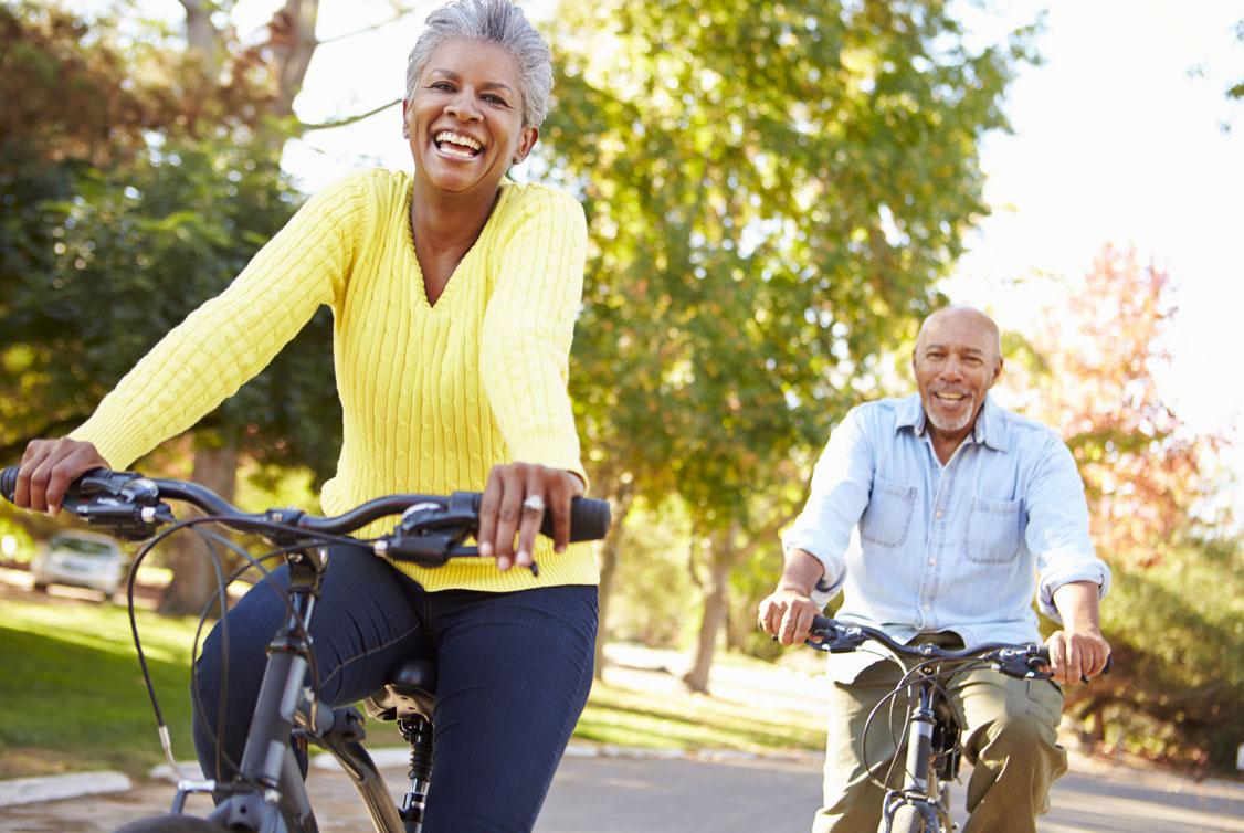 Ein Mann und eine Frau fahren Fahrrädern und lächeln