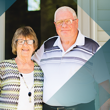 A portrait of Impella patient Jim Hoag and his wife on their front porch with a teal hash background pattern
