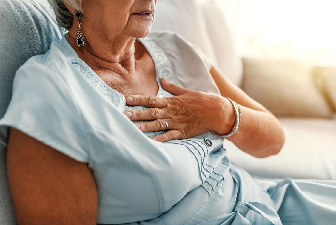Ältere Frau in hellblauem Kleid, die sich ans Herz fasst