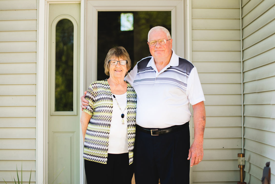 Portrait of Impella patient Jim Hoag and his wife standing on their doorstep