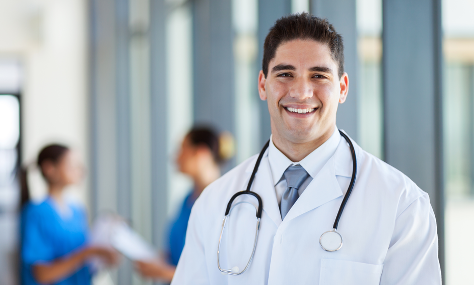 Portrait of a young doctor in a white coat standing in front of colleagues