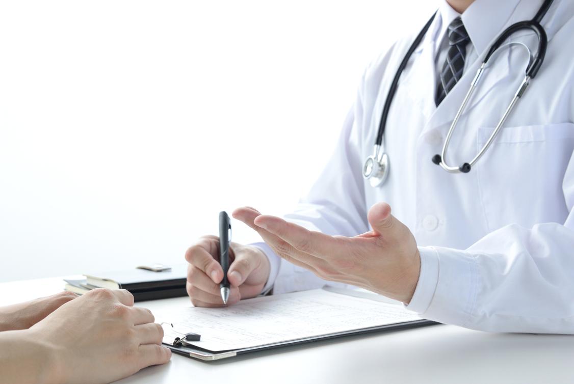 Arzt schreibt etwas über Herzerkrankung in eine Patientenakte