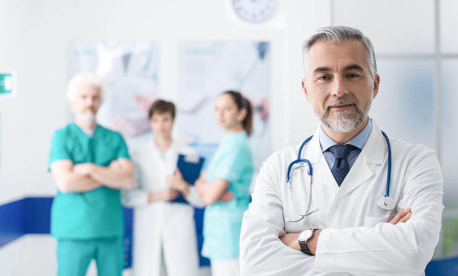 Arzt mit verschränkten Armen im Vordergrund, drei Pfleger und Pflegerinnen im Hintergrund