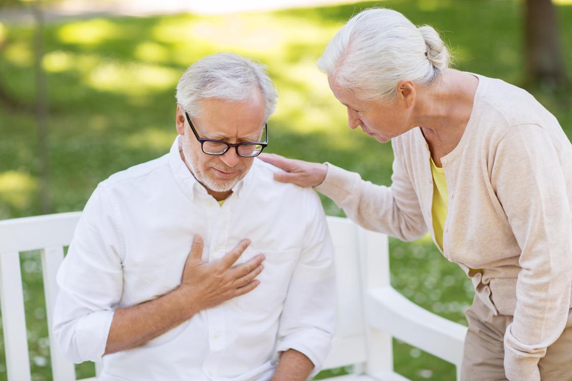 Mann, der auf einer Bank sitzt und sich ans Herz fasst und Frau, die besorgt guckt
