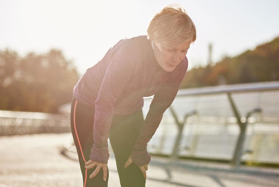 Erschöpfte Frau in Sportkleidung auf einer Brücke