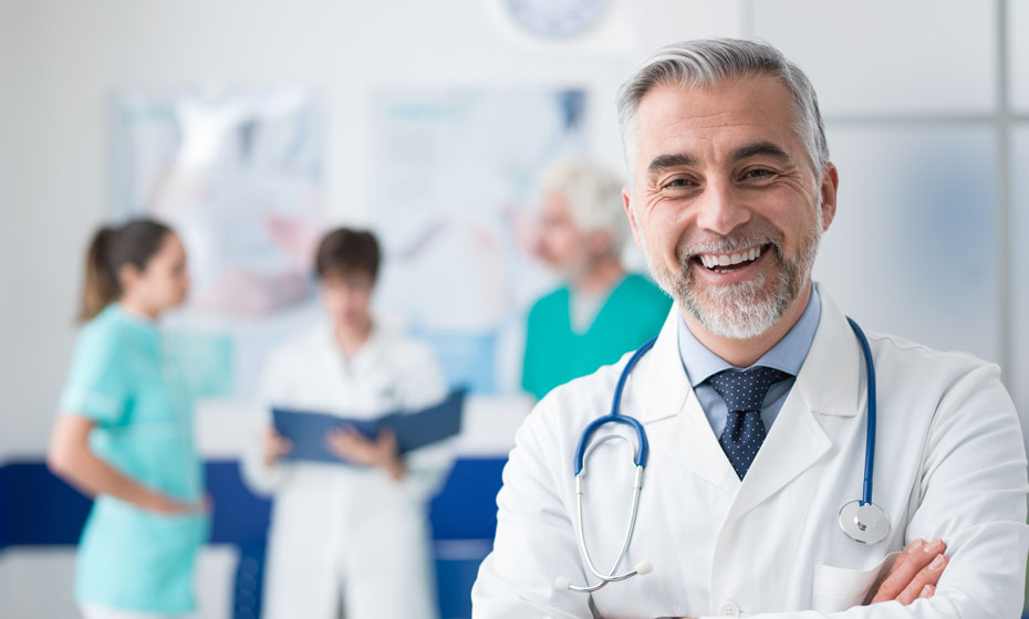 Image of a male physician in front of a group of physicians in a clinical setting