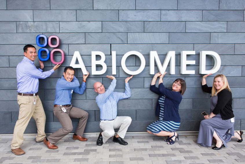 Image of Abiomed employees at the Danvers headquarters in front of the Abiomed sign
